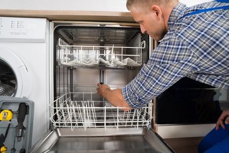 service technician repairing a dishwasher